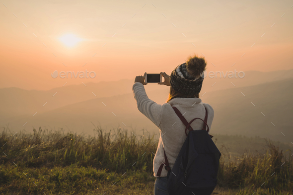 Young traveler taking photo beautiful landscape sunset - Stock Photo - Images