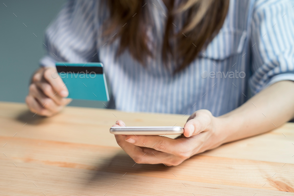 Young woman holding a credit card and using smartphone - Stock Photo - Images
