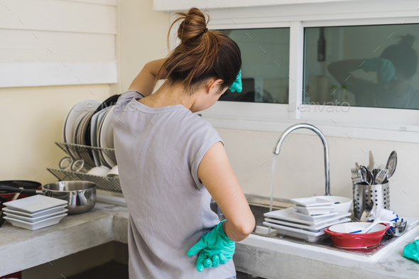 Tired young woman with gloves washing dishes - Stock Photo - Images
