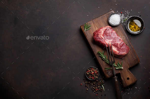 Raw ribeye beef steak cooking with ingredients - Stock Photo - Images