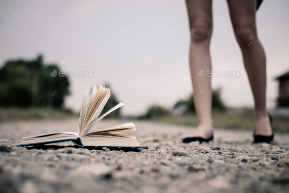 open book lying on the road. - Stock Photo - Images