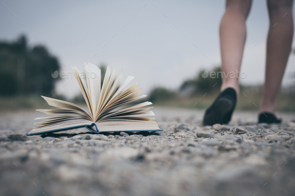 open book lying on the road - Stock Photo - Images