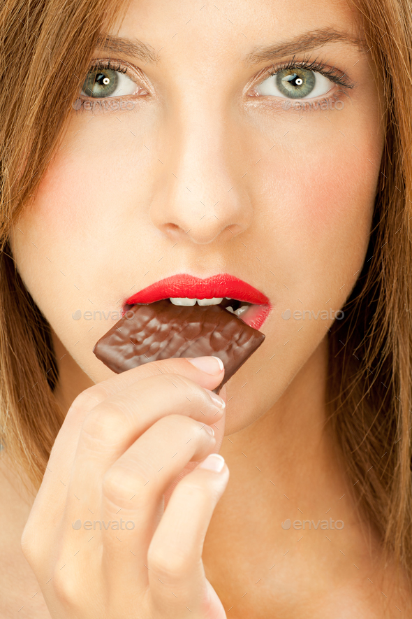 attractive blonde studio portrait eating chocolate - Stock Photo - Images