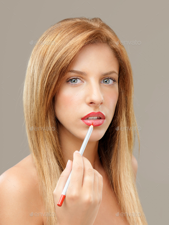 young blonde woman drawing lip contour - Stock Photo - Images