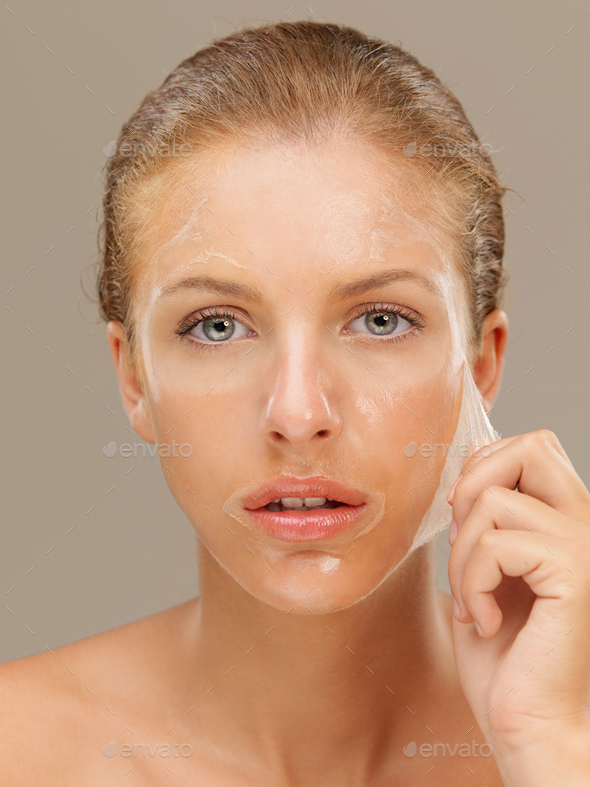 young woman peeling off a facial mask - Stock Photo - Images