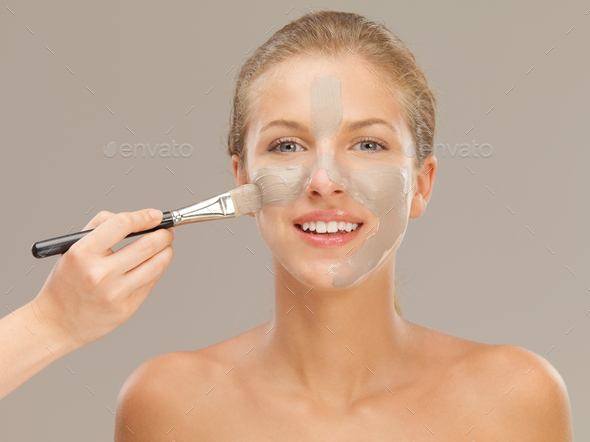 beautiful woman applying mud mask with brush - Stock Photo - Images