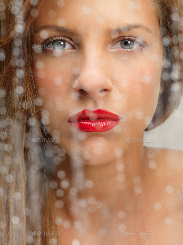 beauty portrait of woman behind wet window - Stock Photo - Images