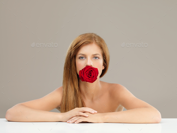 beautiful woman holding red rose in mouth - Stock Photo - Images