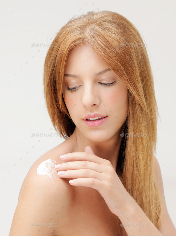 blonde woman applying body lotion on shoulder - Stock Photo - Images
