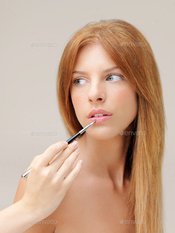 makeup artist applying lipstick on beautiful woman - Stock Photo - Images