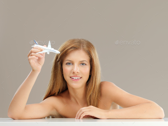 beautiful woman playing with airplane model smiling - Stock Photo - Images