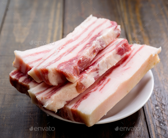 pieces of Iberian bacon on wooden board - Stock Photo - Images