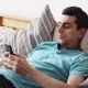 Young Middle Eastern Male Using a Smartphone, Lying on Bed at Home - VideoHive Item for Sale
