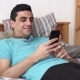 Happy Arabic Man Using a Smartphone, Lying on Bed at Home - VideoHive Item for Sale