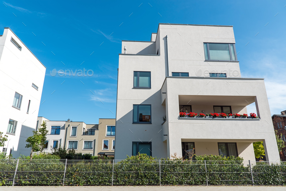 White modern houses in front of a blue sky - Stock Photo - Images