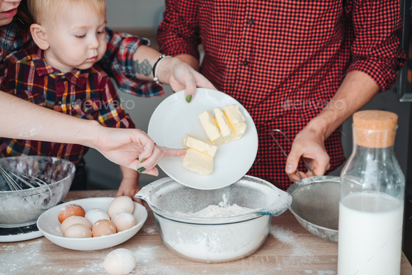 Mom adds butter to flour - Stock Photo - Images