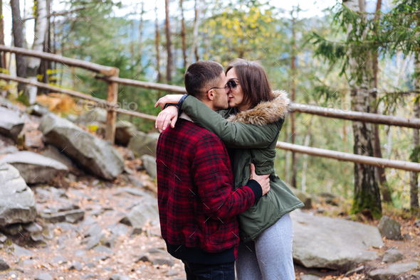 girl and a young man kissing in the woods - Stock Photo - Images