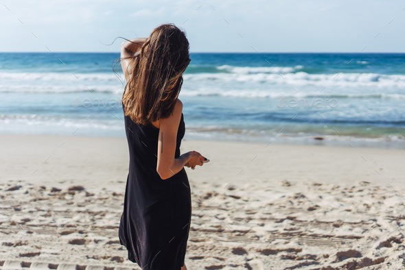 Young beautiful girl looks afar at sea - Stock Photo - Images