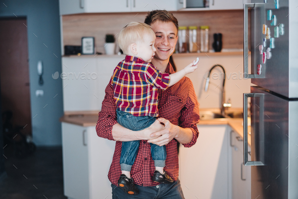 Dad and little son in the kitchen by the fridge - Stock Photo - Images