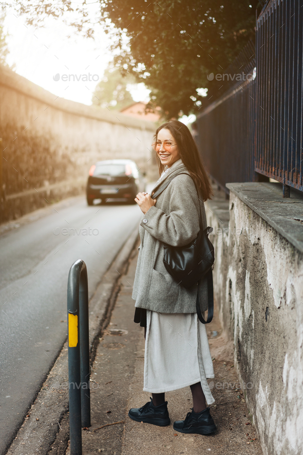 Beautiful young girl on a narrow street. - Stock Photo - Images