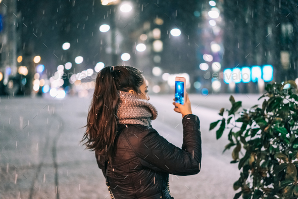 Stylish woman holding phone in city street - Stock Photo - Images