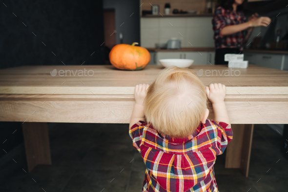 little boy is standing by the table - Stock Photo - Images