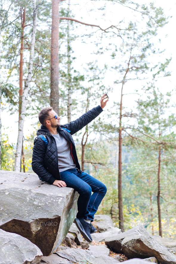 guy sits in the woods on a rock - Stock Photo - Images