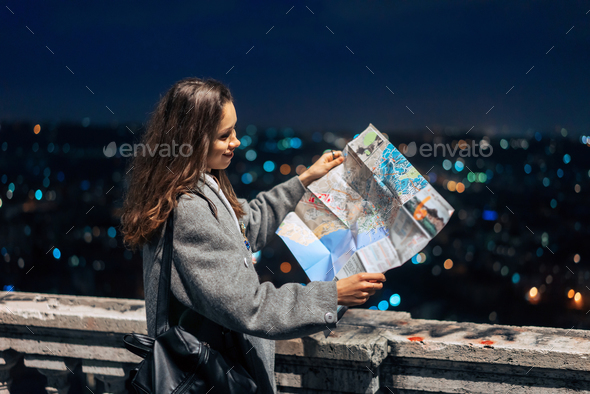 girl with a map on the background of the night city - Stock Photo - Images