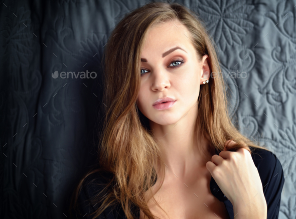 Portrait of a beautiful young woman with long hair looking at ca - Stock Photo - Images