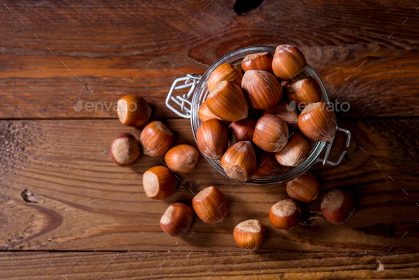 unpeeled hazelnuts in a glass jar, on rustic wood - Stock Photo - Images