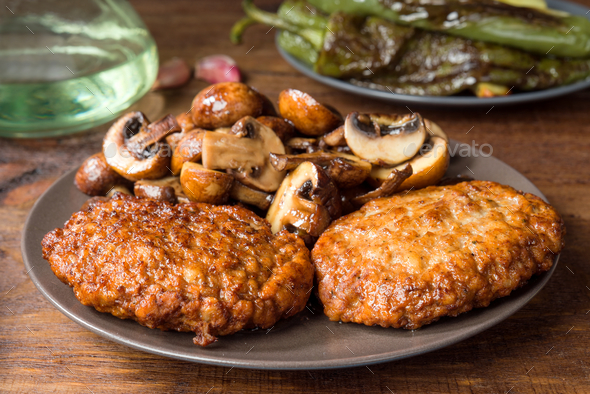 homemade burgers and mushrooms grilled on rustic wood - Stock Photo - Images