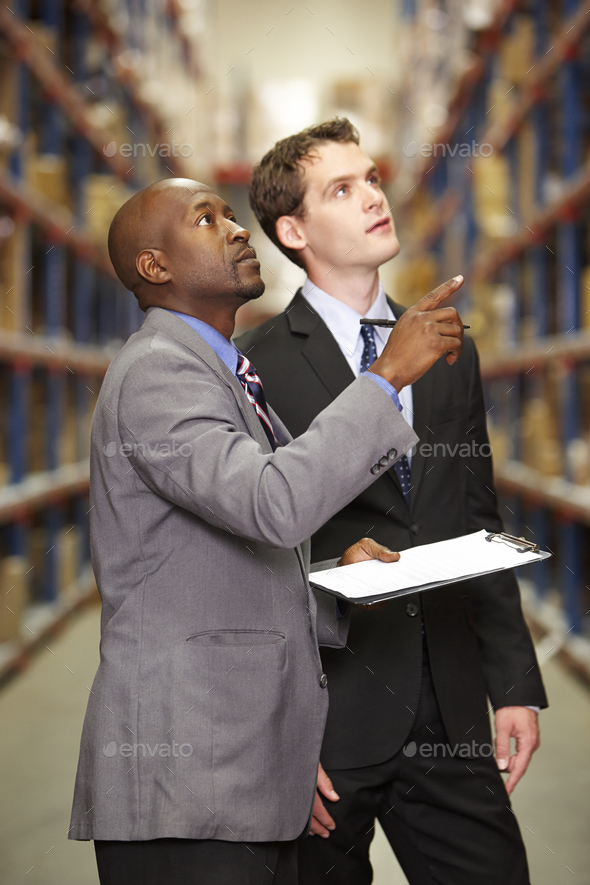 Two Businessmen Having Discussion In Warehouse - Stock Photo - Images