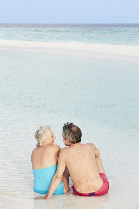 Rear View Of Senior Couple Sitting On Beautiful Beach - Stock Photo - Images