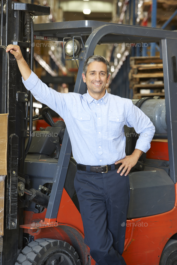 Portrait Of Man With Fork Lift Truck In Warehouse - Stock Photo - Images