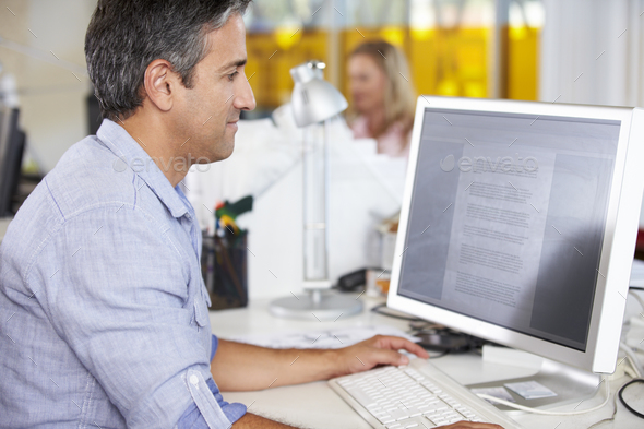 Man Working At Desk In Busy Creative Office - Stock Photo - Images