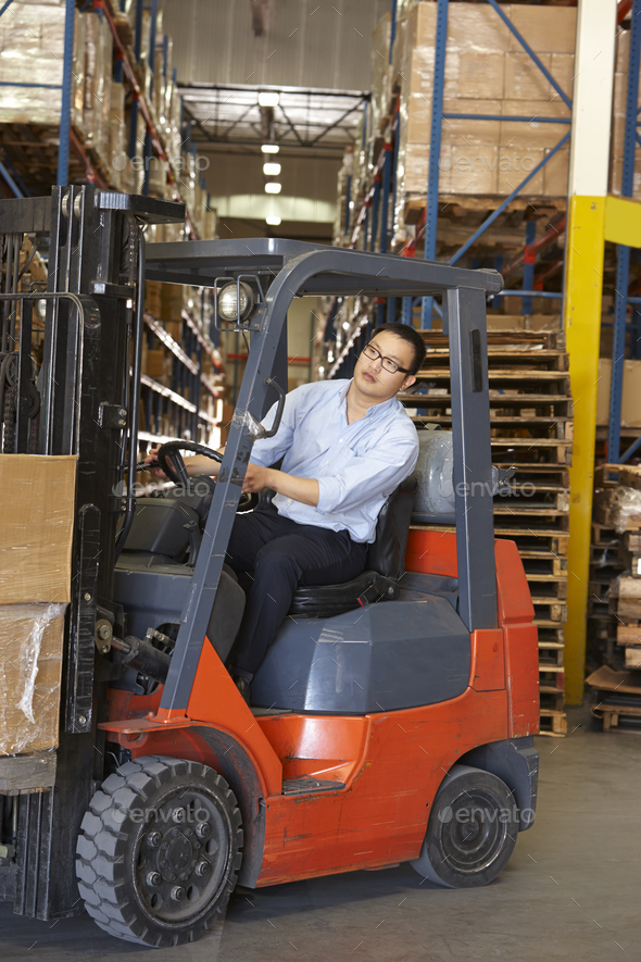 Man Driving Fork Lift Truck In Warehouse - Stock Photo - Images