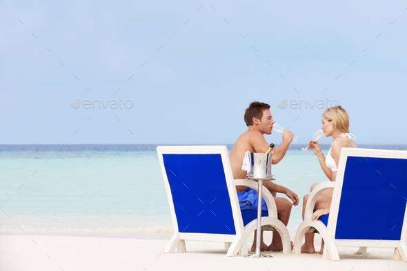 Couple On Beach Relaxing In Chairs And Drinking Champagne - Stock Photo - Images