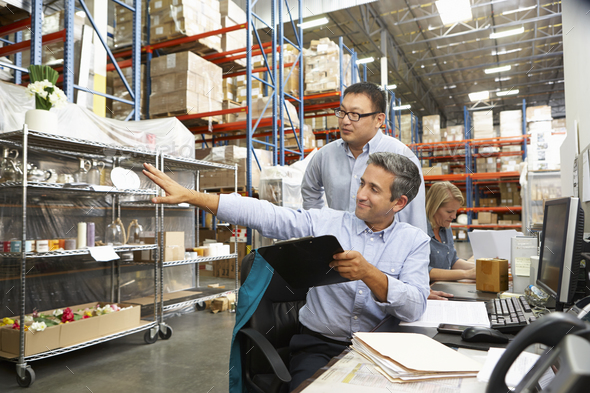 Business Colleagues Working At Desk In Warehouse - Stock Photo - Images