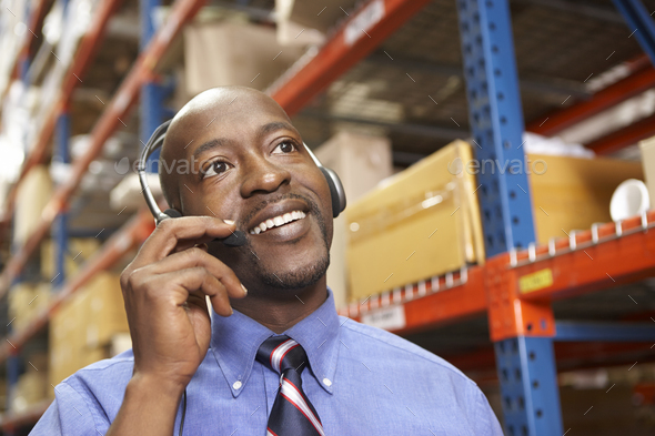 Businessman Using Headset In Distribution Warehouse - Stock Photo - Images