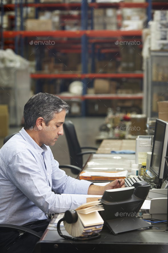 Manager Working At Desk In Warehouse - Stock Photo - Images