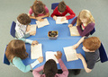 Overhead View Of Schoolchildren Working Together At Desk - PhotoDune Item for Sale
