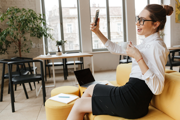 Excited business woman make selfie by mobile phone - Stock Photo - Images