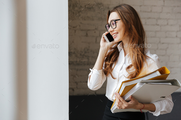Cheerful business woman indoors talking by mobile phone - Stock Photo - Images