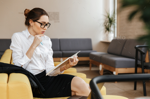 Serious business lady reading documents - Stock Photo - Images