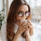Cute business woman sitting indoors drinking coffee - PhotoDune Item for Sale