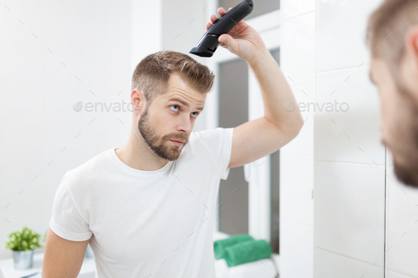 Handsome man cutting his own hair with a clipper - Stock Photo - Images