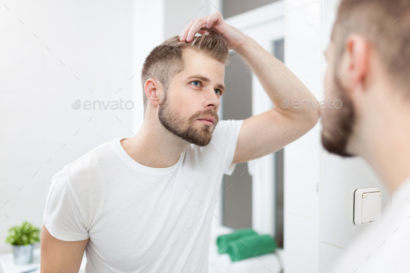 Handsome young man worried about hairloss - Stock Photo - Images