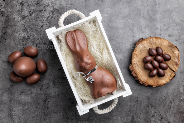 Chocolate Easter bunny and eggs on rustic background - Stock Photo - Images