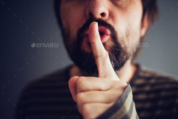 Man saying hush or be quiet - Stock Photo - Images