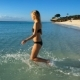 Girl in Bikini Swims in the Indian Ocean at Sunset on a Lonely Tropical Beach - VideoHive Item for Sale